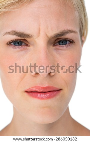 Serious blond woman looking at camera on white background - stock photo