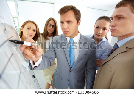 Serious boss pointing at whiteboard surrounded by his colleagues - stock photo
