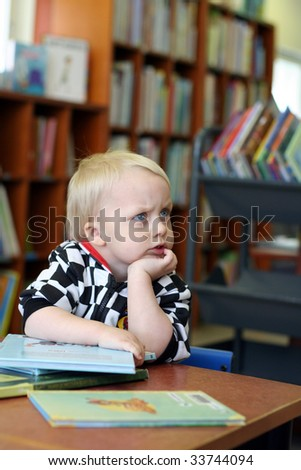 Serious boy in the library - stock photo