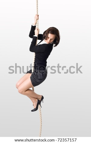 Serious business lady on the rope looking down - stock photo