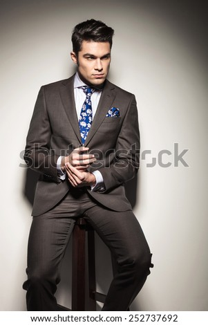 Serious business man holding his hands together while looking away from the camera, sitting on a stool against studio background. - stock photo