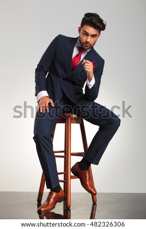 serious business man in elegant double breasted suit sitting on a chair on grey studio background