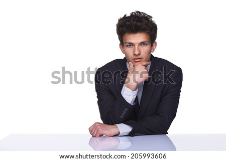 Serious business man sitting on table with hand on chin, over white background