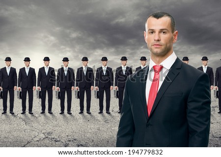 Serious  business man standing in front of his team - stock photo