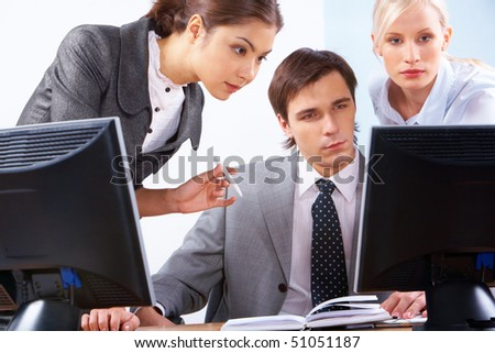 Serious business people looking at computer screen during corporate meeting