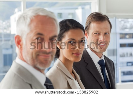 Serious business people looking in the same way in their office - stock photo