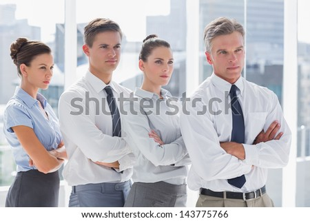Serious business people standing together in line in a modern office