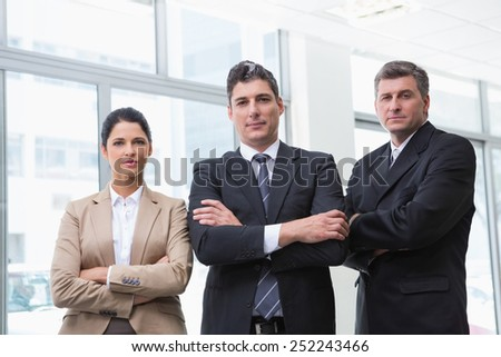 Serious business team standing with arms crossed at new car showroom - stock photo