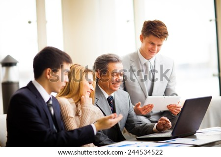 serious business team with tablet pc computers, documents having discussion in office - stock photo