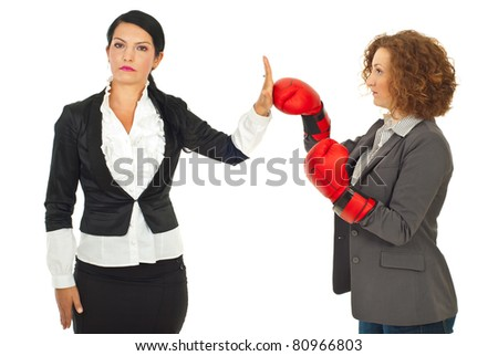 Serious business woman give stop hand to her colleague woman with boxing glove isolated on white background - stock photo