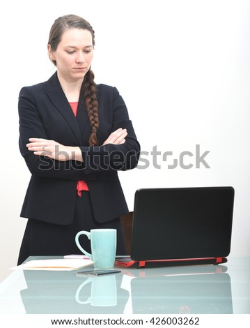Serious business woman looking at computer with arms crossed - stock photo