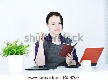 Serious business woman with notebook and pen - stock photo