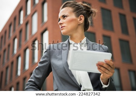 Serious business woman with tablet pc in front of office building - stock photo