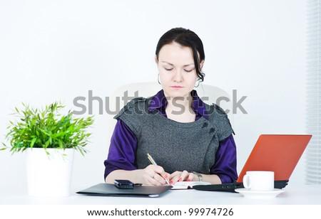 Serious business woman writing - stock photo