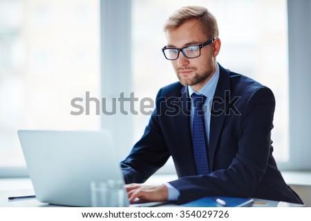 Serious businessman analyzing electronic data - stock photo