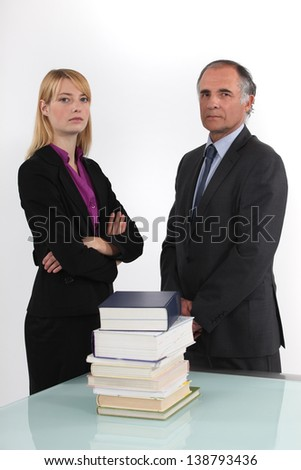 serious businessman and businesswoman posing next to pile of books - stock photo