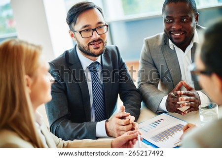 Serious businessman answering his colleagues questions at meeting - stock photo