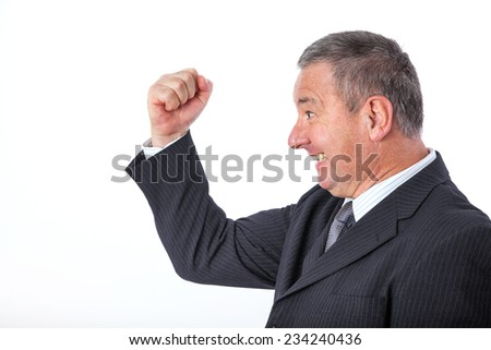 Serious businessman clenches his fist with joy - stock photo
