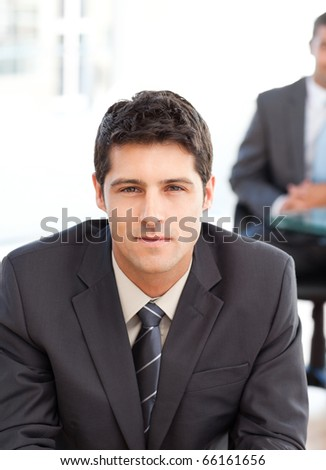 Serious businessman during an interview with a co-worker waiting in the background - stock photo
