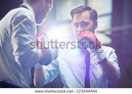 Serious businessman in boxing gloves looking at his rival before attack - stock photo