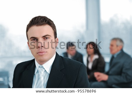 Serious businessman in company with colleagues
