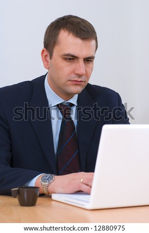 Serious businessman in his office working on white lap-top