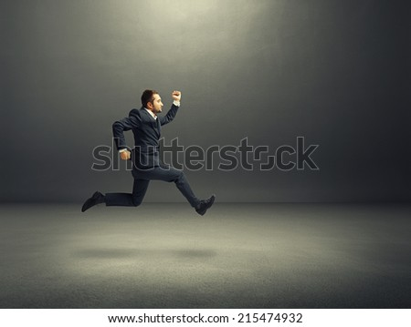 serious businessman in suit running fast in the dark room - stock photo