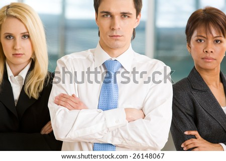 Serious businessman looking at camera between two smart females