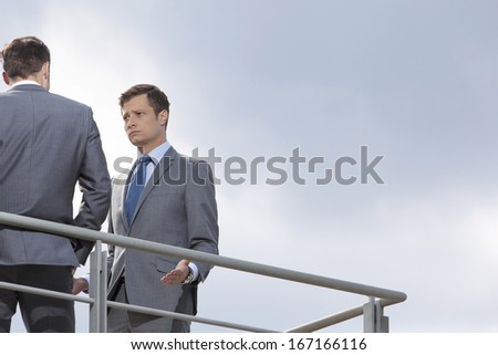 Serious businessman looking at coworker against clear sky - stock photo