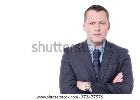 Serious businessman posing to camera with crossed arms
