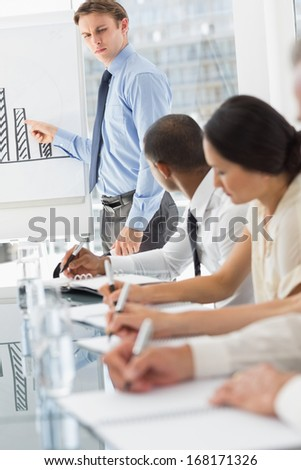 Serious businessman presenting bar chart in meeting in the office