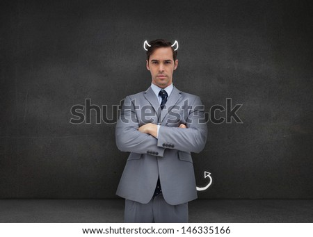 Serious businessman representing the demon on grey background - stock photo
