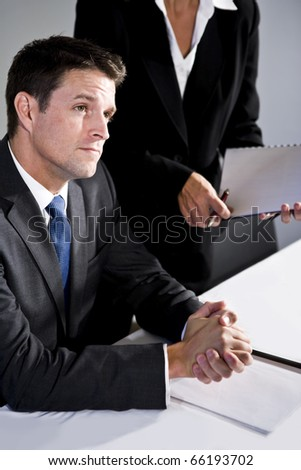 Serious businessman, 30s, watching presentation, female assistant standing beside