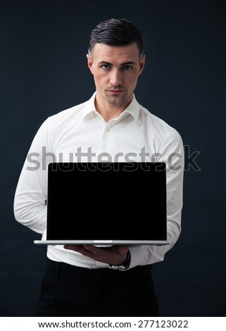 Serious businessman showing blank laptop screen over black background and looking at camera - stock photo