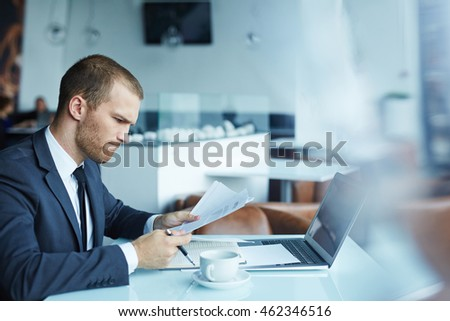 Serious businessman sitting at the table and working with documents