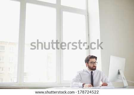 Serious businessman sitting in office and networking - stock photo