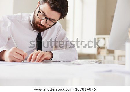 Serious businessman sitting in office and working - stock photo