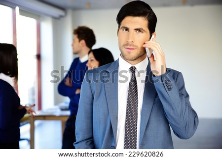 Serious businessman talking on the phone in front of colleagues - stock photo