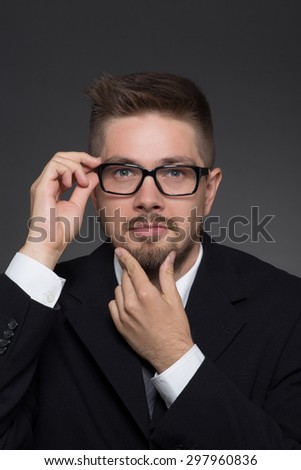 Serious businessman touching his glasses on dark grey. Handsome man in black business suit keeping his beard.