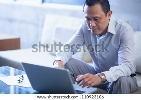 Serious businessman typing on laptop in office - stock photo