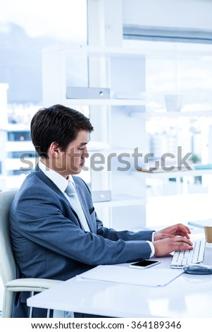 Serious businessman using his computer in his office - stock photo