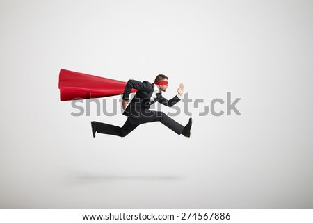 serious businessman wearing like superhero very fast running over light grey background - stock photo