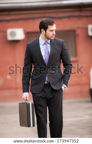 serious businessman with a briefcase walking on the street - stock photo