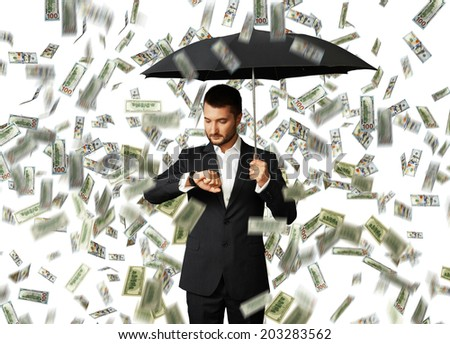 serious businessman with black umbrella standing under money rain and looking at watch - stock photo