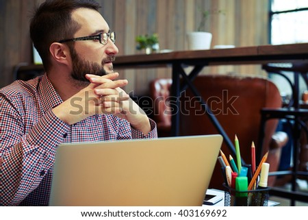 Serious businessman with glasses sitting behind a table on his laptop and looking away and taking hands in the castle - stock photo