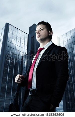 serious businessman with red tie in front of skyscrapers