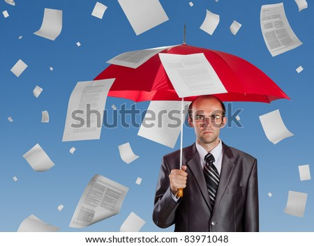 Serious businessman with red umbrella under falling documents