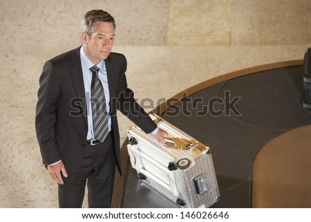 Serious businessman with suitcase at luggage carousel in airport - stock photo