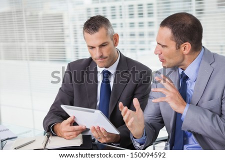 Serious businessmen analyzing documents on their tablet in bright office - stock photo