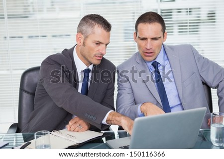 Serious businessmen working on their laptop in bright office